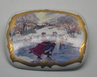 W11: Vintage Hand Painted Ceramic Christmas Ice Skating in Snow Scene Brooch
