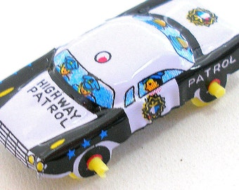 60s tin toy police car, vehicle in black & white. Made in Japan.