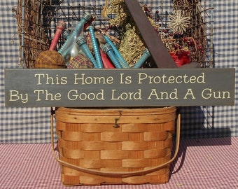 """Primitive rustic sign This Home Is Protected By The Good Lord And A Gun painted wood  farmhouse sign 4"""" x 24"""" choice of color"""