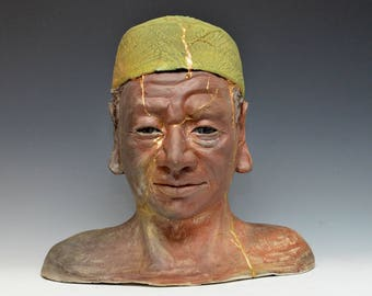 African Buddha Figurative Sculpture With a Sea Green Cap With Gold