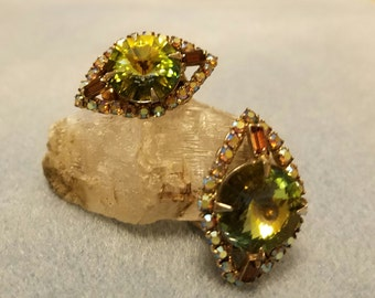 "Elegant vintage 1950s diamond shaped clip earrings with beautiful ""aurora borealis"" rhinestones in greens, golds, and browns."