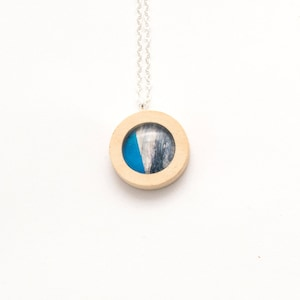 Wooden suspension . Round Pendant of wood and glass . The texture of wood and dark blue .
