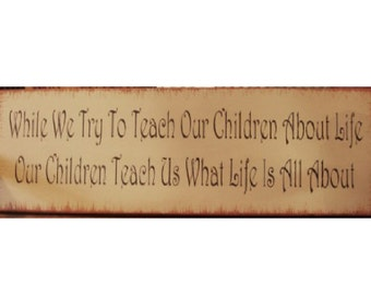 While we try to teach our children about life our children teach us what life is all about wood sign
