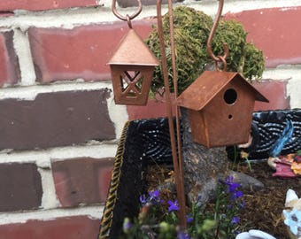 A copper color hanging lantern or birdhouse for your miniature garden or terrarium.  Each come with mini Sheppard hook