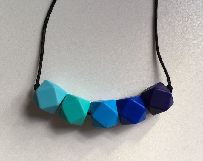 Teething necklace in navy, ultramarine, sky blue, turquoise, azure; made from BPA free chewable silicone hexagon beads by Little Gnashers