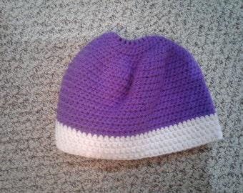 A handmade crocheted teenage purple messy bun hat with a whitestripe