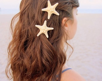 Two small white knobby starfish barrettes.
