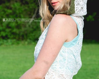 White lace vest with hood. Sequined floral lace is slightly sheer. Hood is trimmed in olive green lace. Size small.