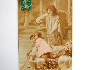 The guardian angel protecting the card-children french vintage 1900-sepia photo postcard colorized by hand