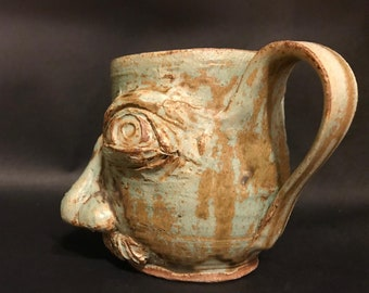 Green face on a mug