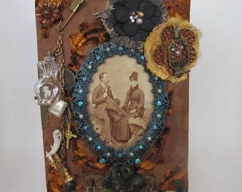 Orange velvet  altered album  embellished with found objects and mounted on metal frame