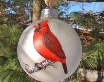 Northern Cardinals, one male, one female, on birch twigs.  Handpainted on silver matte ball ornament.