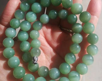 A strand of Siberian Chatoyant/ cat's eye nephrite beads
