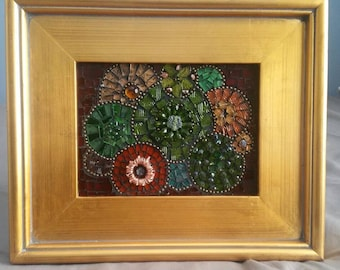 This is a stained glass mosaic using different shades of greens, browns and golds with accents of glass beads.
