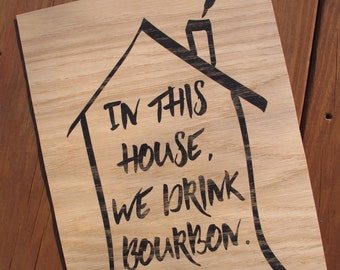 "Wood print ""in this house we drink bourbon"""
