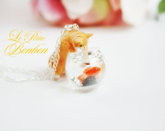Mischievous Yellow Kitty cat is playing with goldfish in a fish bowl necklace