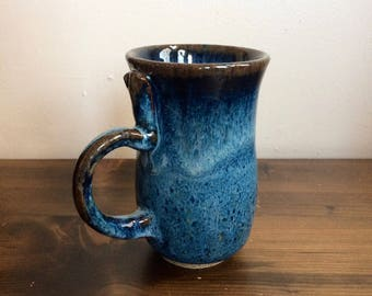 Speckled stoneware mug in drippy blue glaze