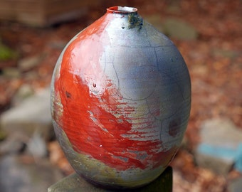 Round blue raku vase  or bottle shape in blue and blue-gray tones with dramatic red brushstrokes. Small to medium size