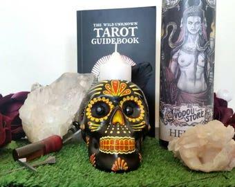 Hand painted dia de los muertos skull candle holder in yellow/orange tones