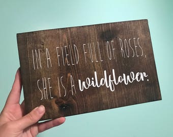 In a field full of roses, she is a wildflower sign