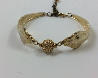 "Royal Sealey. Gold plated spoon bracelet, gold bead, lobster claw clasp, safety chain, size medium (7.5"")"