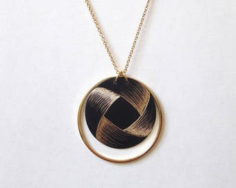Round brass necklace, blackened hand with a decorative pattern reminiscent of a Ribbon.