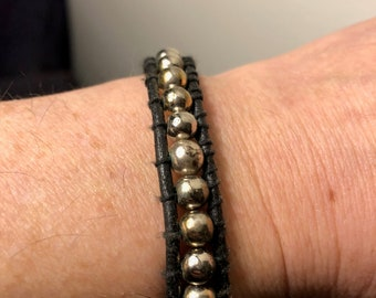 Black leather ladder-stitch bracelet with steel beads and tribal-style closure