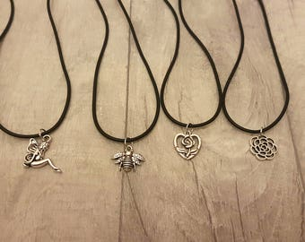 Child friendly Silver Coloured Charm Necklace. Finished With A Sleek Black Rubber Feel Chain.