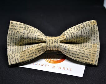 Handmade bow tie for men made up of light brown cotton fabric and writings