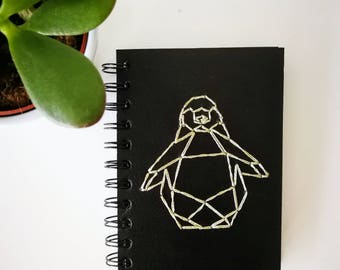 Embroidered notebook with a penguin.