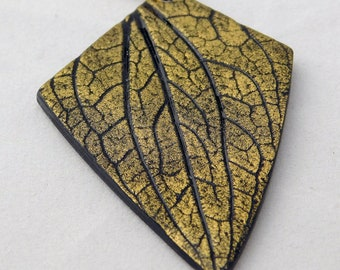 Elegant black and gold pendant with leaf imprint