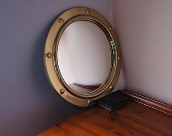 Vintage brass convex nautical mirror.