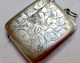 Vintage vesta box with ring so could be wore on a chain with keepsakes. Decorative metal collectable match box.