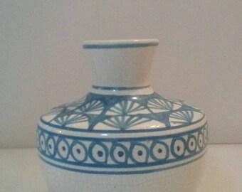 White ceramic die-cut and turquoise vase