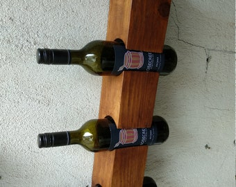 Wall wine rack for three bottles.