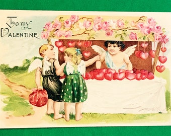 Antique 1900s Valentines Day Postcard, A Little Cherub Giving Bunches Of Little Red Hearts, A Lovely Embossed Holiday Post Card