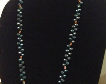 vintage black cultured freshwater pear shaped long strand pearl necklace with 14k yg lock. circa 1980