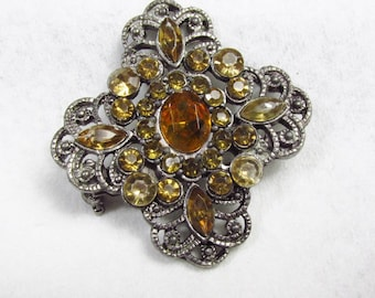Vintage 1940s pot metal amber colored rhinestones brooch pin.
