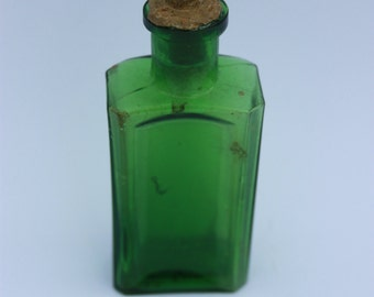 Small green glass bottle with ribbed corners
