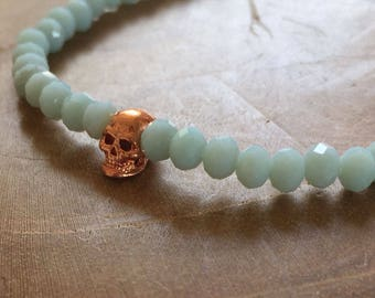 Pale Blue faceted Skull: elastic beaded bracelet with rosegold skull and blue glass beads. pastel, facet, rosegoldtone, skull, rock, edgy