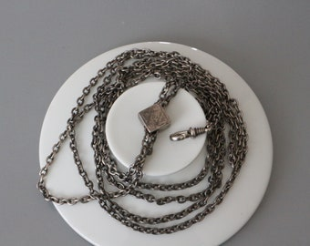 Elegant massive solid silver antique ladies watch/muff chain with a slider.