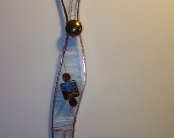 clear glass with copper bead on top with flower bead in middle