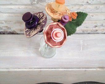 peach, purple, and mauve button flower bottle bouquet