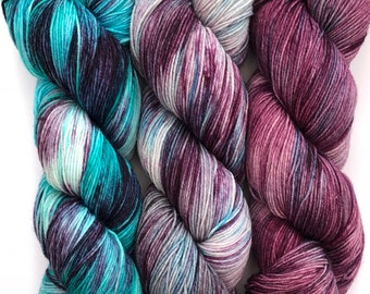 A beautifully coordinating set of hand dyed yarns on a merino, nylon base in purples and blues.