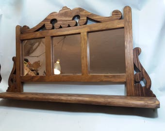 Rustic wooden shelf with three mirrors.