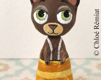 Mini brown bear in overalls and yellow