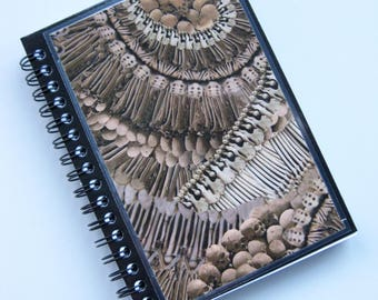 "Alexander McQueen A6 (11x15cm) spiral-bound notebook made with ""Catacomb' print paper."