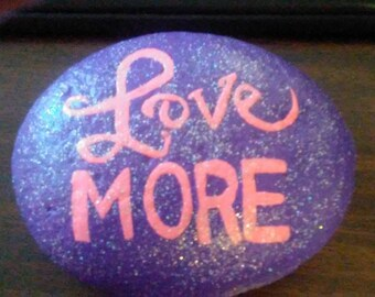 Love More in pink paint on rich purple background with sparkles