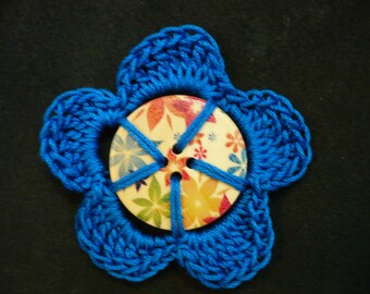 Flower crocheted around a colorful wooden button