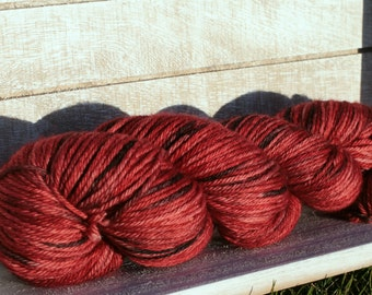 Hand dyed worsted weight yarn in red and black coloryway, Indie yarn in a worsted weight wool, Merino superwash wool dyed